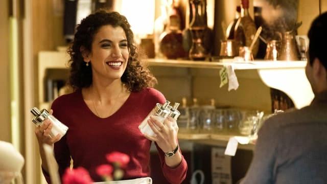 Eine Szene aus dem Film mit Zahraa Ghandour: Als Amal arbeitet sie in einem Café, sie hält Zuckerstreuer in der Hand und lacht.