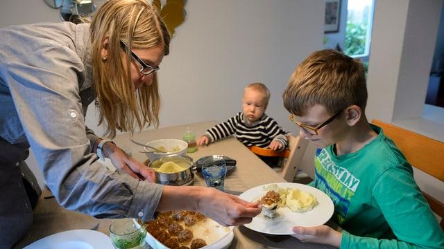 Mutter mit zwei Kindern am Esstisch. Sie serviert das Essen.