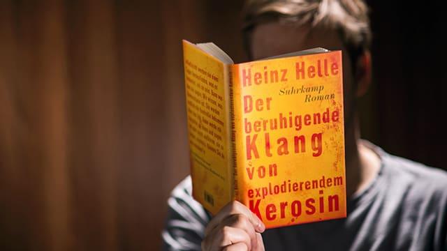 Mann hält Buch vor Gesicht.