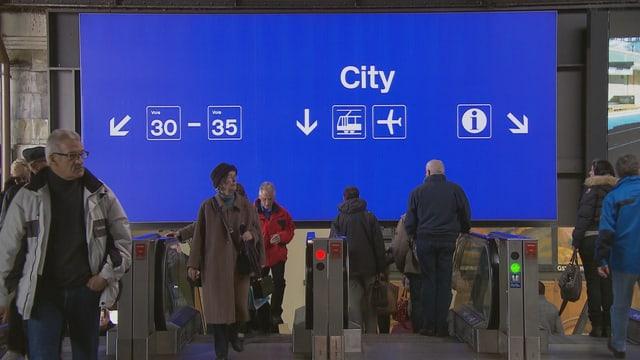 Eine grosse blaue Tafel mit verschiedenen Angaben wie City, Perronnummern und Flughafenzeichen im Basler Bahnhof.