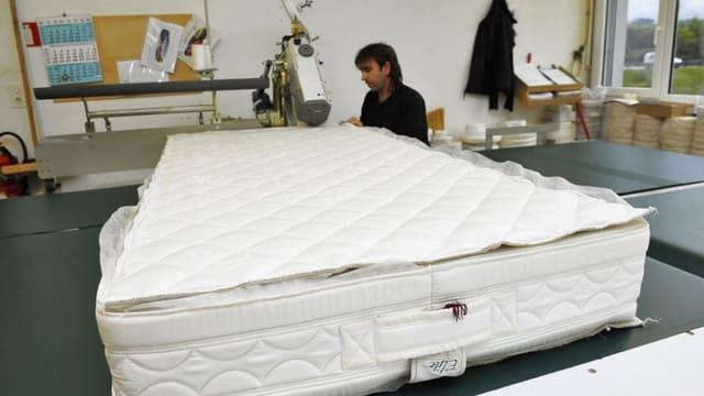 Ein Mitarbeiter der Farbrik in Aubonne näht eine Matratze zusammen.