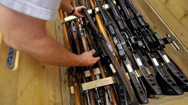 Eine Person befüllt eine Kiste mit Waffen