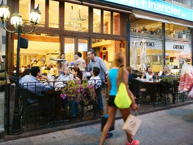 Ein Strassencafe in Beirut, eine junge Frau in kurzen Hosen läuft vorbei.