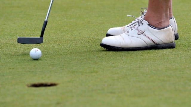 Ein Golfball steht wenige Zentimeter vor einem Golfloch.
