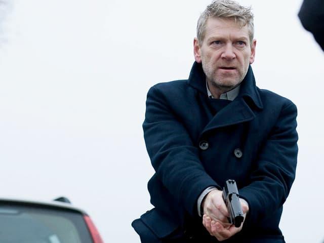 Kenneth Branagh als Kommissar Wallander im schwarzen Mantel und mit Pistole in der Hand.
