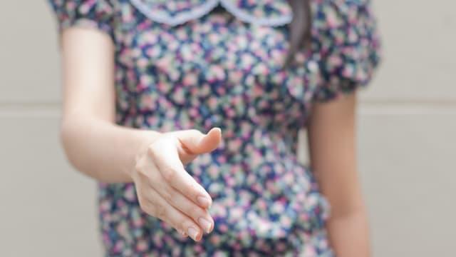 Zum Gruss ausgestreckte Frauenhand