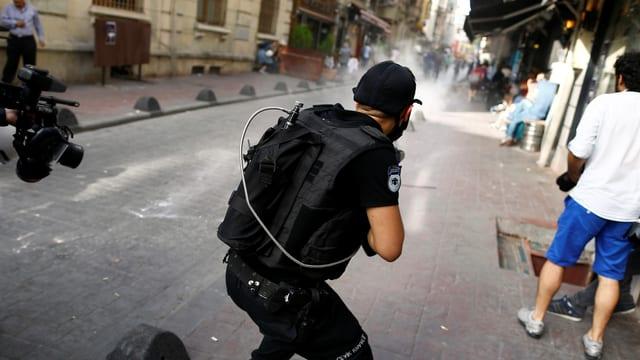 Ein Polizist schiesst mit Gummischrot.