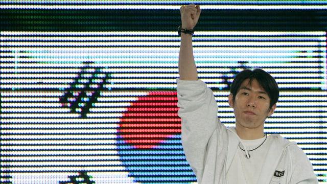 Junger Koreaner vor einem Bildschirm mit der koreanischen Flagge.