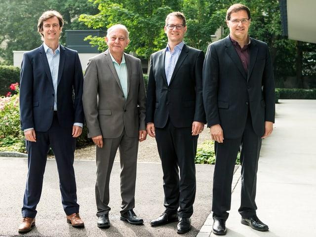 Vier Männer stehen neben einander und posieren für die Kamera.