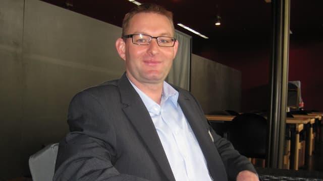 Ein Mann in Anzug mit Brille, blonden Haaren und blauen Augen sitzt in einem Sessel.