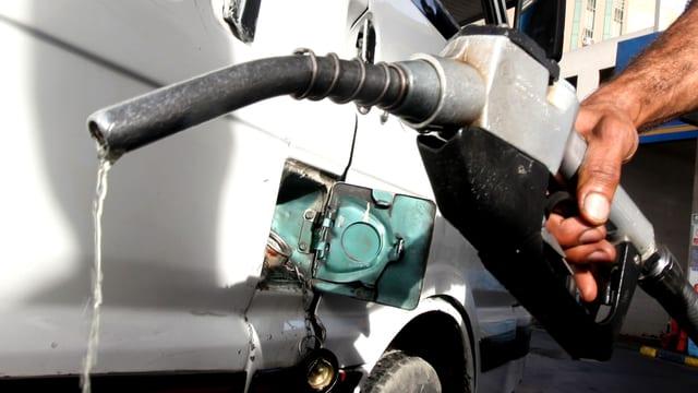 Ein Mann füllt Benzin in den Tank.