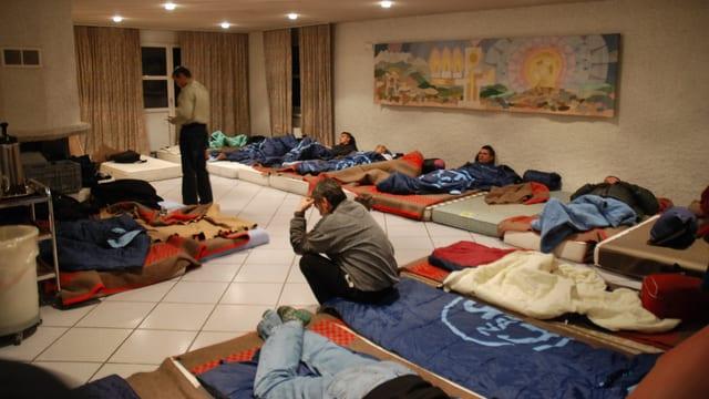 Junge Männer liegen auf Betten am Boden in einem grossen Raum.