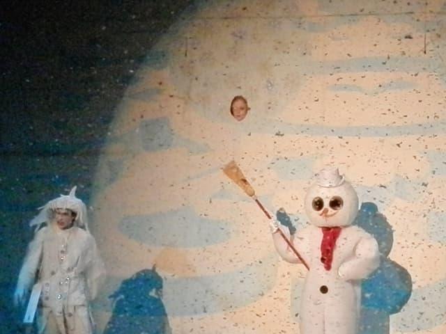 Die weisse Figur des Winters und ein Schneemann, aus einem Gucklock schaut ein Kind.