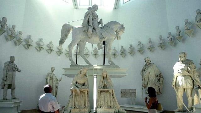 Die Skulptur eines Reiters aus weissem Marmor im Museum. Zwei Leute schauen hoch zum grossen Kunstwerk.