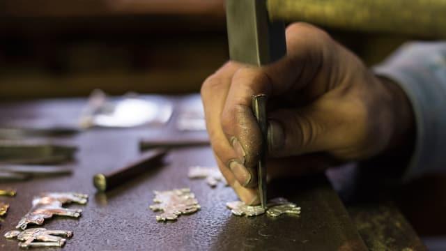 EIne Hand beim kunstvollen Bearbeiten von eines Messingbeschlags.