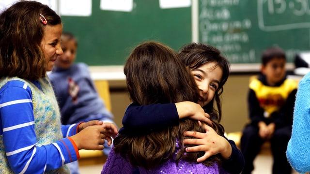 Zwei Mädchen umarmen sich im Klassenzimmer.