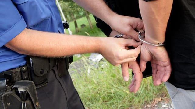 Polizist und Täter in Handschellen