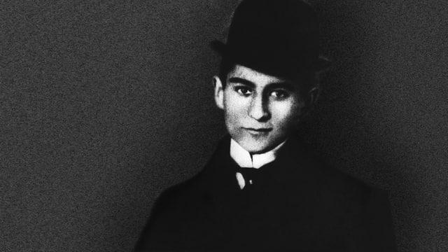 Der junge Franz Kafka mit rundem Herrenhut vor dunklem Hintergrund