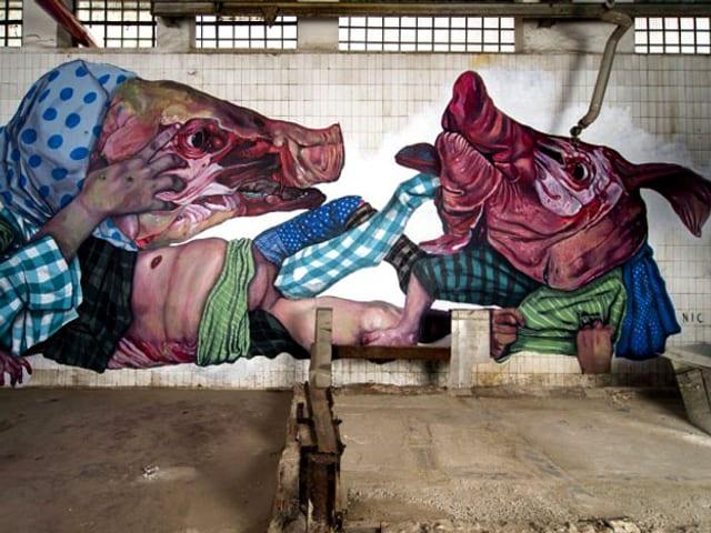 Ein Graffiti an der Wand des MAAM zeigt zwei ineinander verschlungene Schweinsköpfe mit abgezogener Haut.