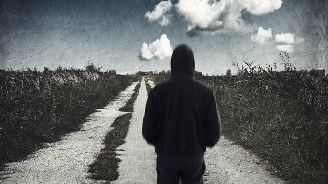 Die Silhoutte eines Mannes der auf einem endlos langen Feldweg steht. Die Atmosphäre des Bildes ist düster.