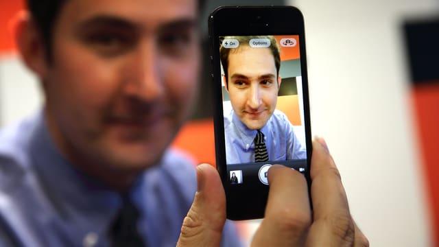 Instagram-CEO Kevin Systrom hält mit einem Porträt von sich selbst auf seinem Handy.