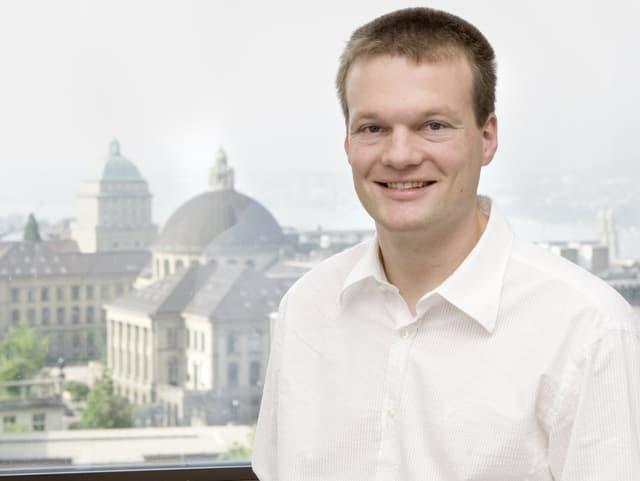Porträt von Reto Knutti, auf seinem Schoss ein Laptop, im Hintergrund das Gebäude der ETH