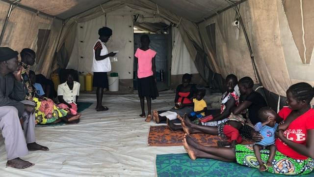 Männer, Frauen und Kinder sitzen am Boden eines Zeltes.