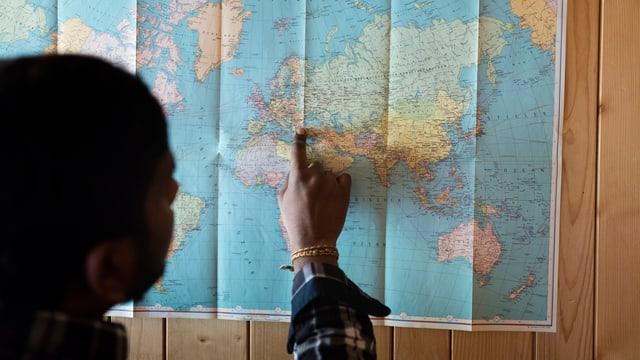 Ein Asylbewerber zeigt auf einer an die Holzwand gepinnten Weltkarte , wie er in die Schweiz gekommen ist.