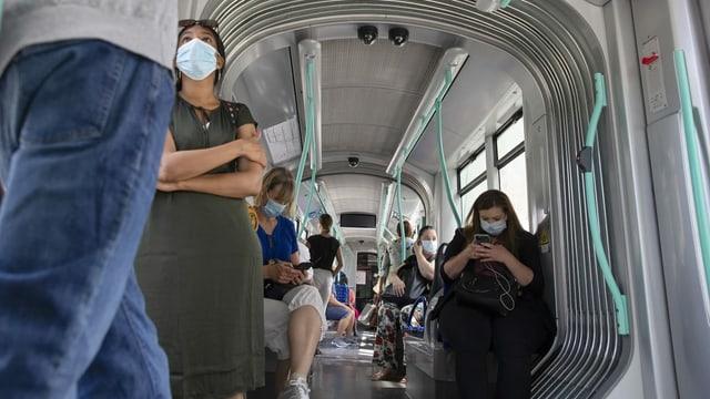 Menschen in einem Tram mit Maske.