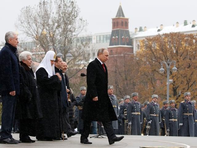 Wladimir Putin läuft zum Rednerpult, umgeben von Gästen und Polizisten.