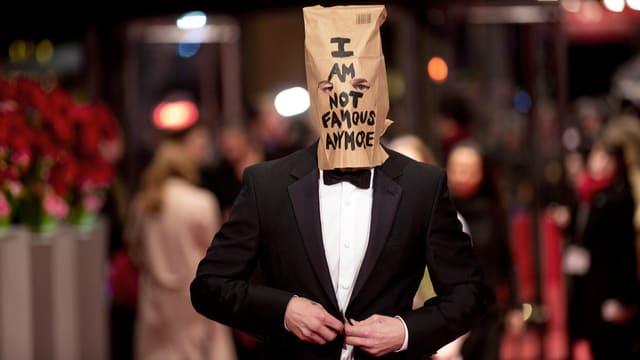 ShiaLaBeouf trägt einen Anzug und einen Karton auf dem Kopf mit der Aufschrift: «I am not famous anymore».