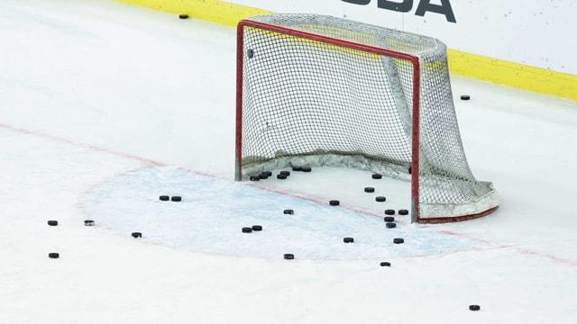 Leeres Eishockey Tor mit Pucks auf dem Eis