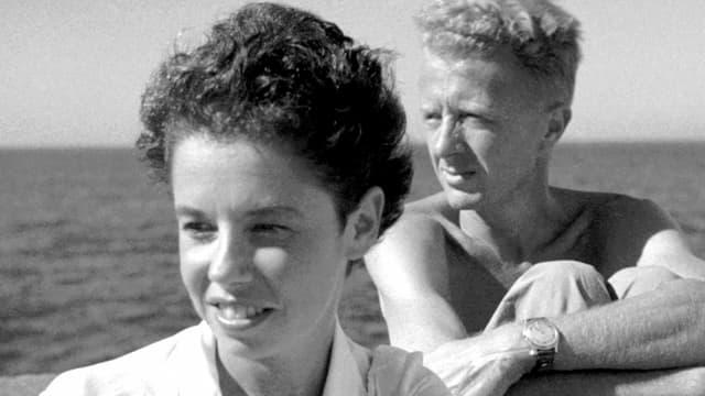 Ein Mann und eine Frau schauen nach links, im Hintergrund das Meer.