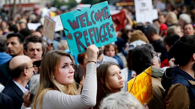 Frau mit Plakat in Menschenmenge: Welcome Refugees