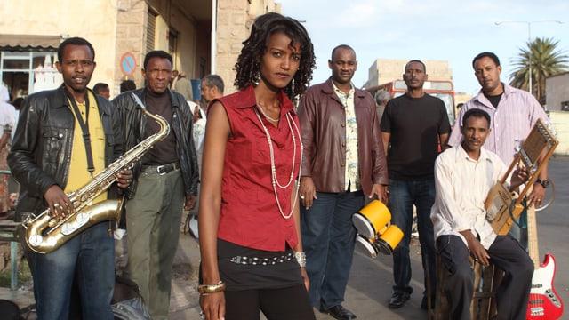 Eine siebenköpfige Band aus Eritrea mit Instrumenten, im Vordergrund die Sängerin.
