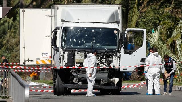 Ein weisser Lastwagen mit Einschusslöchern in der Windschutzscheibe, mehrere Personen in weissen Schutzanzügen stehen darum herum.