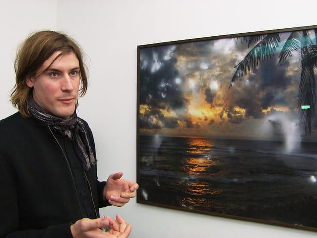 Julian Charrière vor einer Fotografie eines Strandes im Sonnenuntergang mit seltsam aufgehellten Flecken darin.