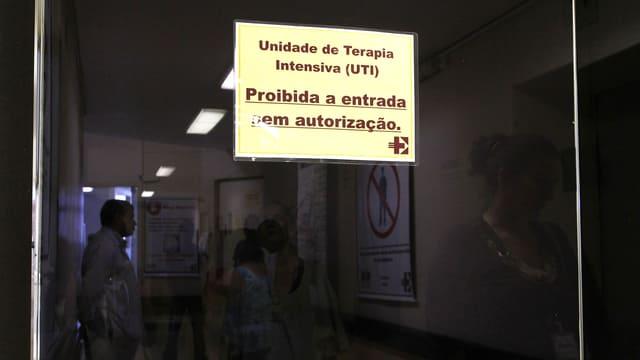Blick auf eine Glastür. Ein Plakat darauf verbietet den Eintritt in die Intensivstation.