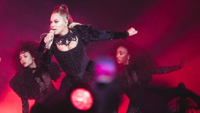 Eine Frau in schwarzem Kleid steht singend mit Mikrofon auf einer Bühne, die in dunkelrotes Licht getaucht ist.