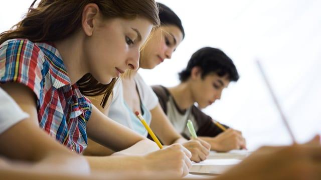 zwei Schülerinnen und ein Schüler sitzen am Pult und schreiben. Man sieht sie alle von der Seite.