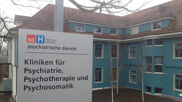 Altes Gebäude, daneben eine Informationstafel, auf der steht: Kliniken für Psychiatrie, Psychotherapie und Psychosomatik
