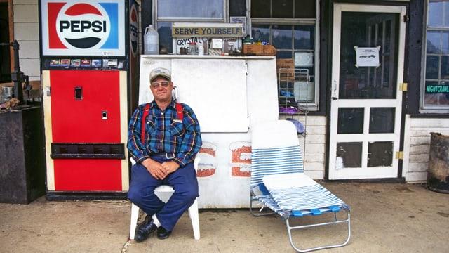 Mann sitzt auf Veranda vor Laden