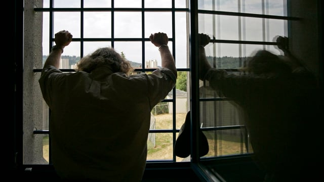Rückenansicht eines Häftlings, der an einem vergitterten Fenster steht.