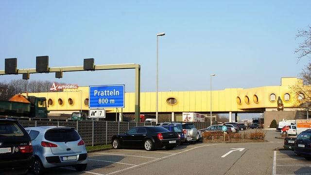 Ein gelbes futuristisches Gebäude erstreckt sich quer über die A2.
