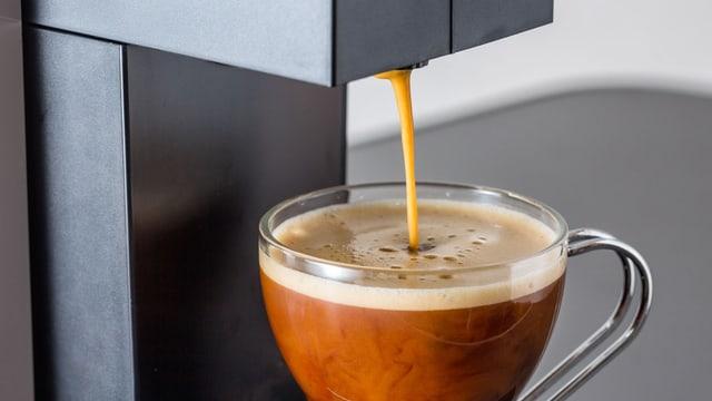 Kaffeemaschine füllt Kaffee in eine Tasse.