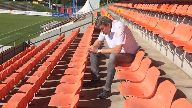Mann auf Sitztribühne in einem Fussballstadion.