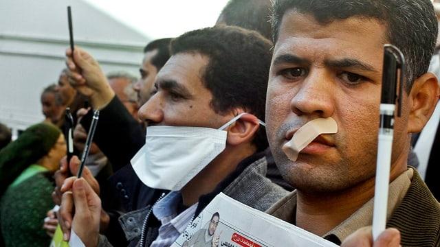 Journalisten demonstrieren in Kairo mit zugeklebten Mündern und hochgehaltenen Kugelschreibern.