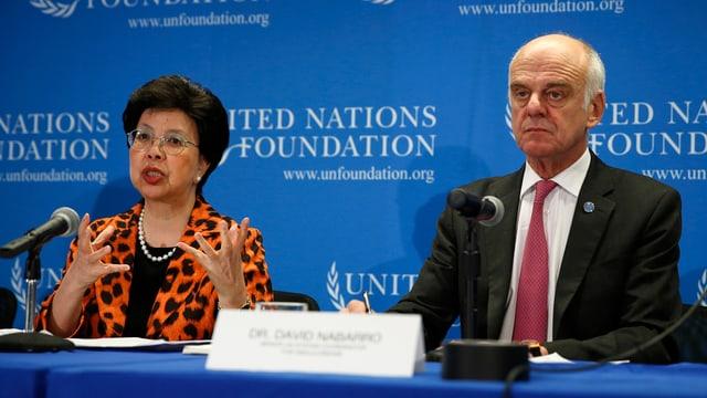 Die WHO-Direktorin Margaret Chan sitzt an einem Tisch und spricht, daneben sitzt ein UNO-Beauftragter