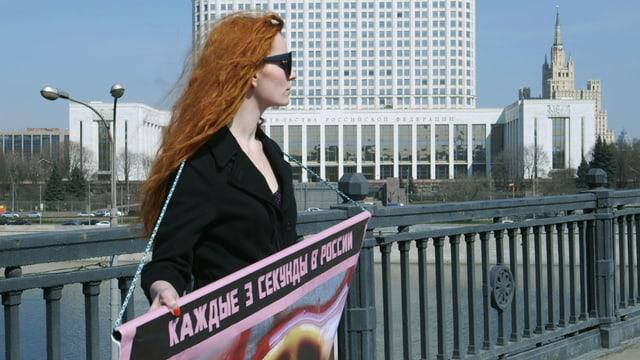 Natalia steht auf der Brücke mit einem Plakat.