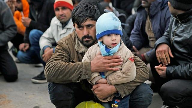 Mehrere Flüchtlinge im Lager in Moria, darunter ein Vater mit seinem kleinen Jungen.